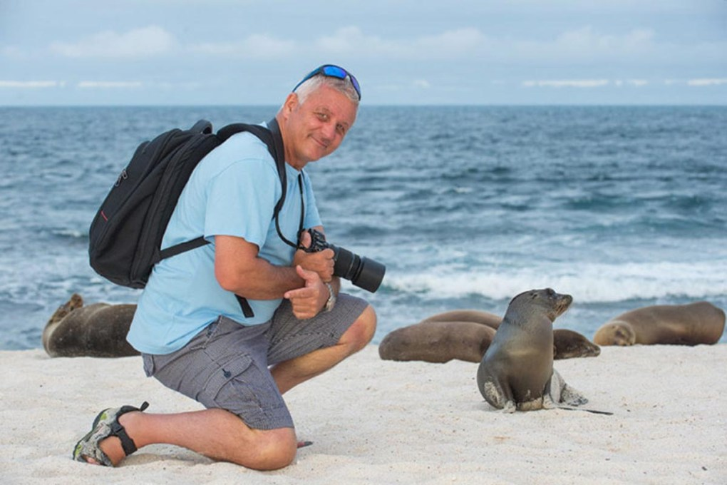 A guest poses with sea lions on a Royal Galapagos LGBTQ travel tour.