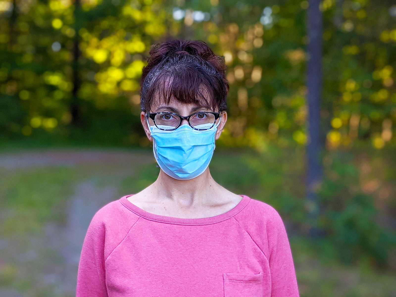 Woman wearing strips of Cabeau Tape to Cabeau tape to keep glasses from fogging up while wearing a mask.
