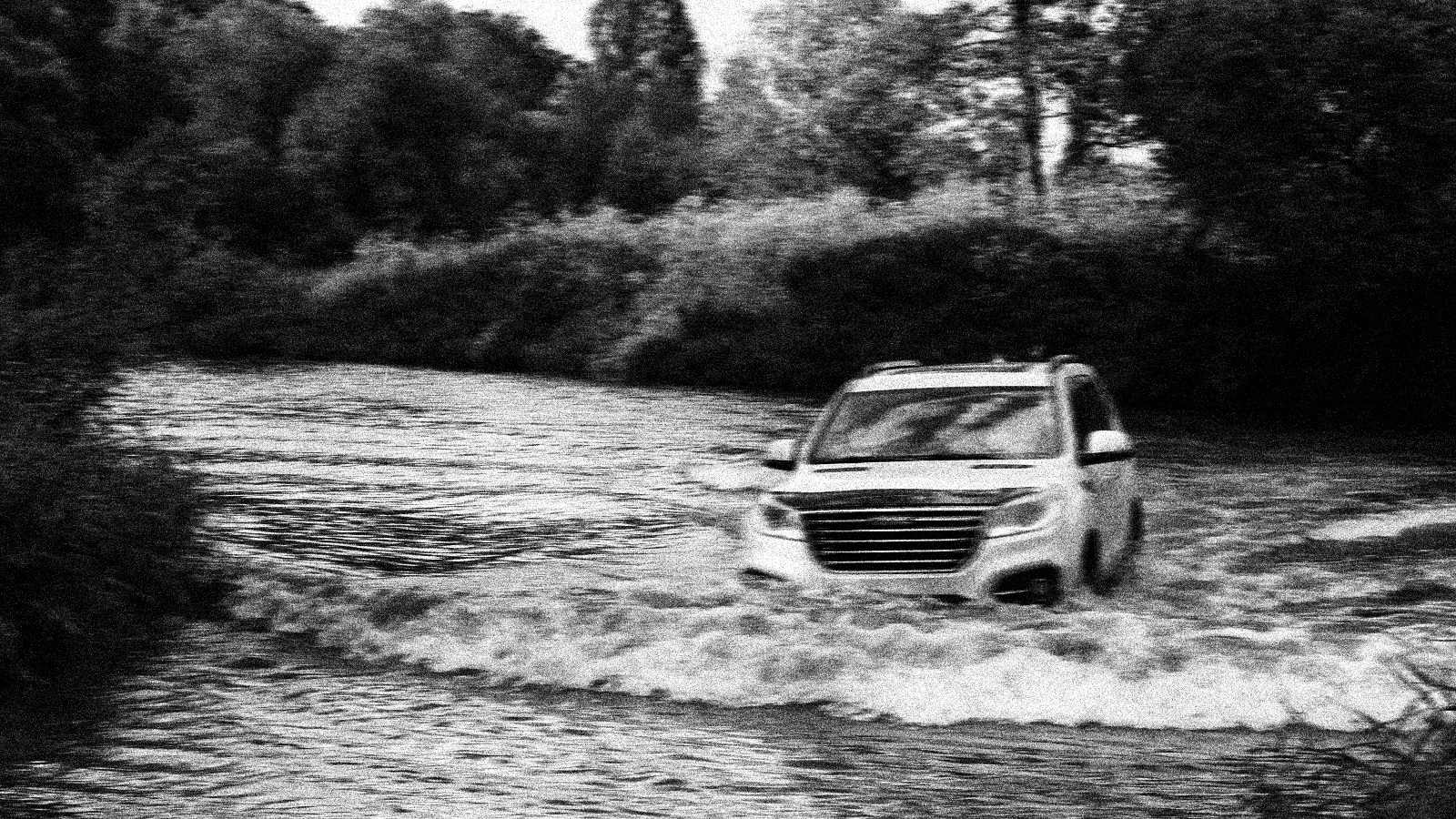 photo of car being washed away on flooded road.
