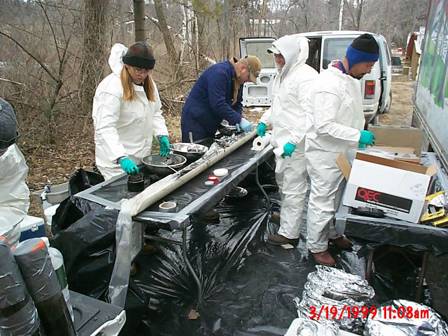 Photo of people in protective clothing March 19, 1999 Sectioning a core sample of soil from near the Housatonic River to test for PCBs.