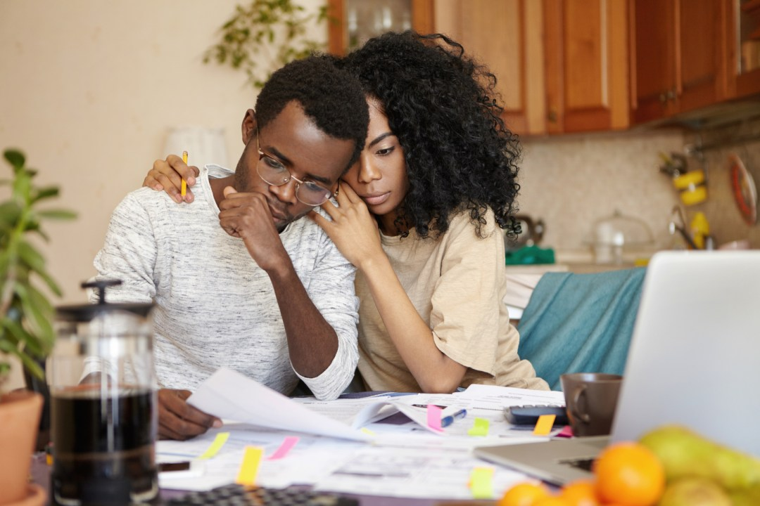 Photo of young couple struggling to balance finances; Shutterstock.