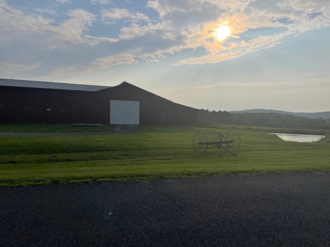 A photo of the afternoon sun over a farm on Baldwin Hill in Egremont, Mass. photo by Isabel Costa.