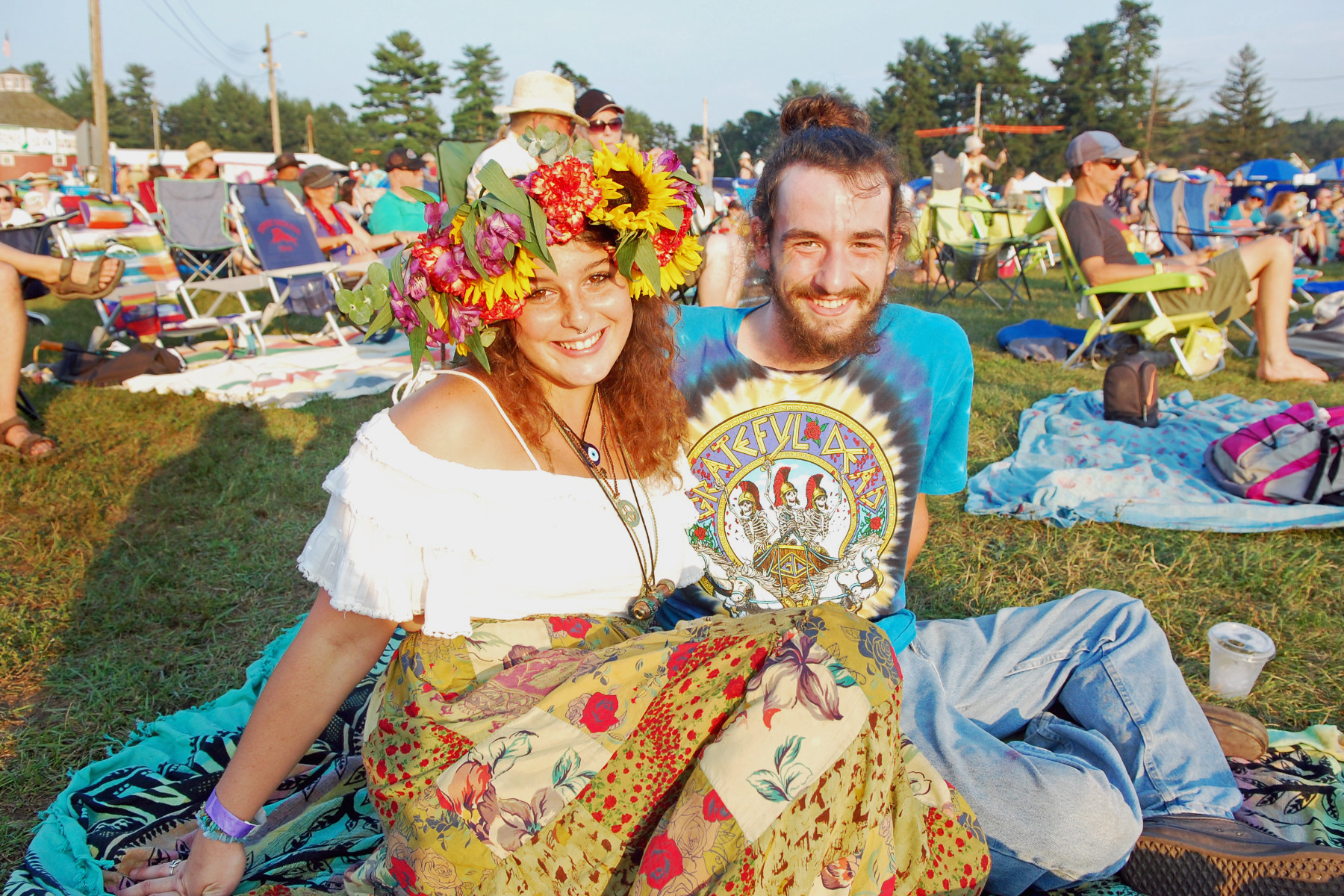 woman and a man sitting on the grass at the Green River Music Festival.