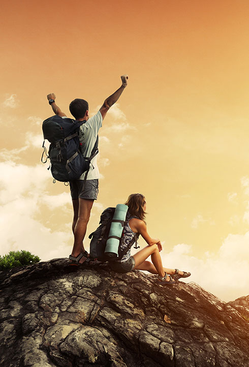Two hikers with backpacks enjoying sunset view from top of a mountain