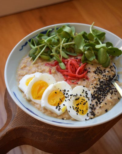 Savory oatmeal with miso topped with egg, seasame seeds, pickled ginger, and sprouts.