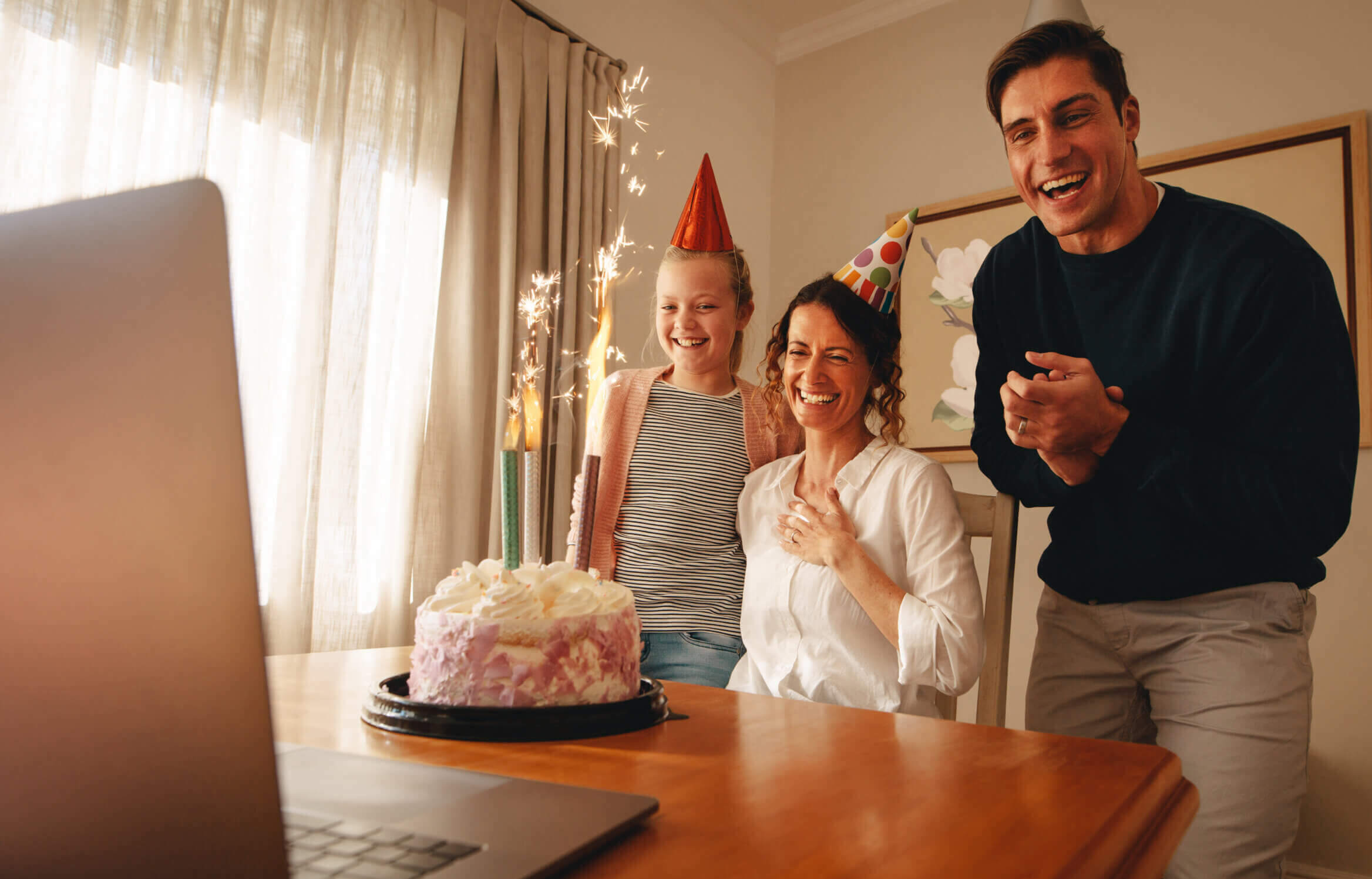 Woman celebrating birthday at home with family and friends on video call. Laptop and birthday cake with candles on table with family wearing party hats smiling at home.