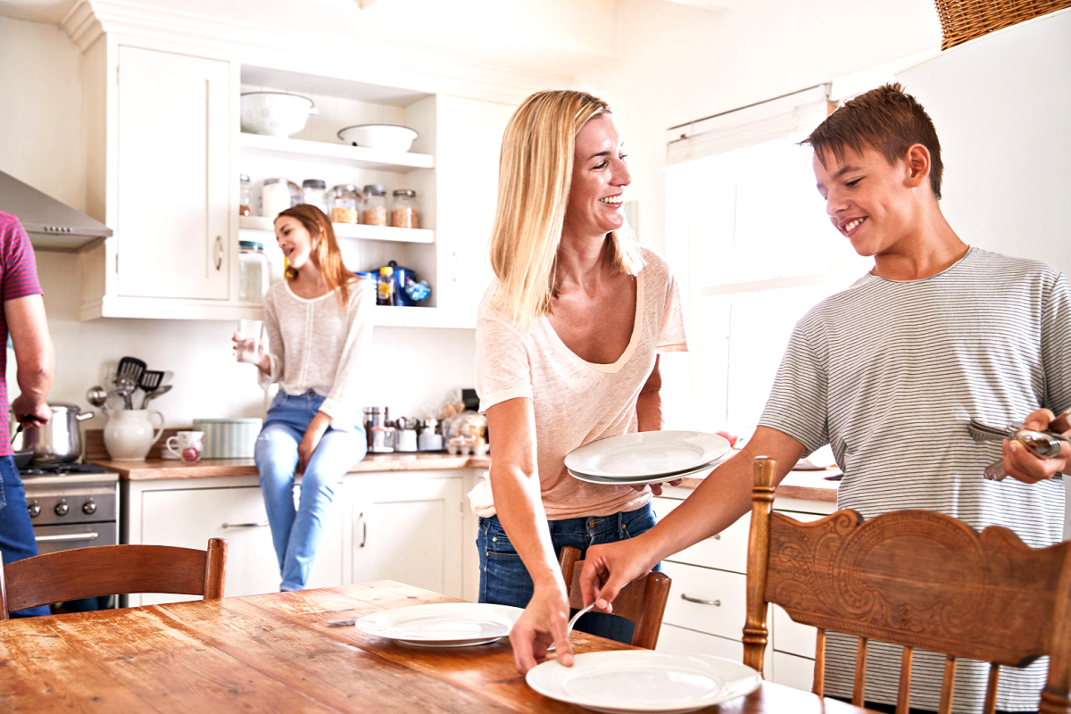 mom and teen boy setting table with teen girl sitting on kitchen counter in the background talking to dad who is cooking