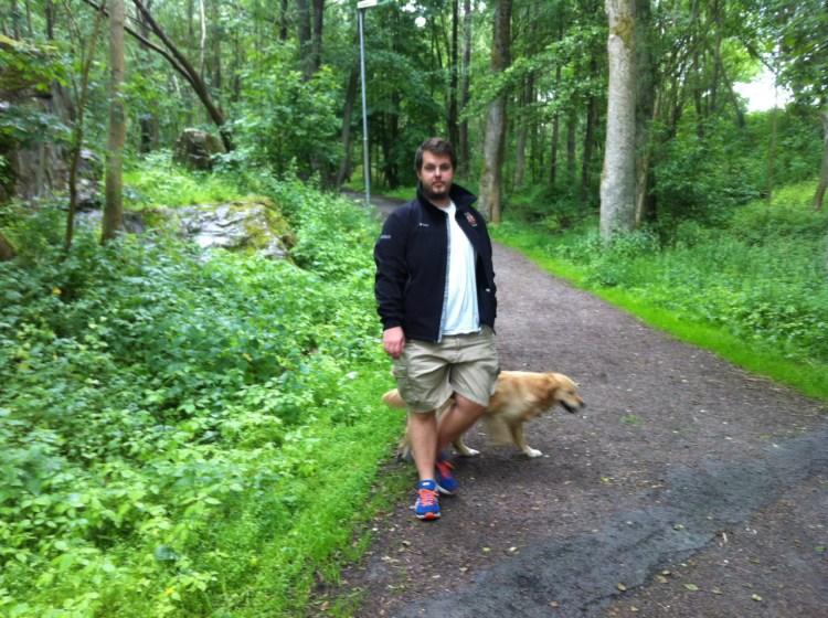 en man och en hund på promenad i skogen.