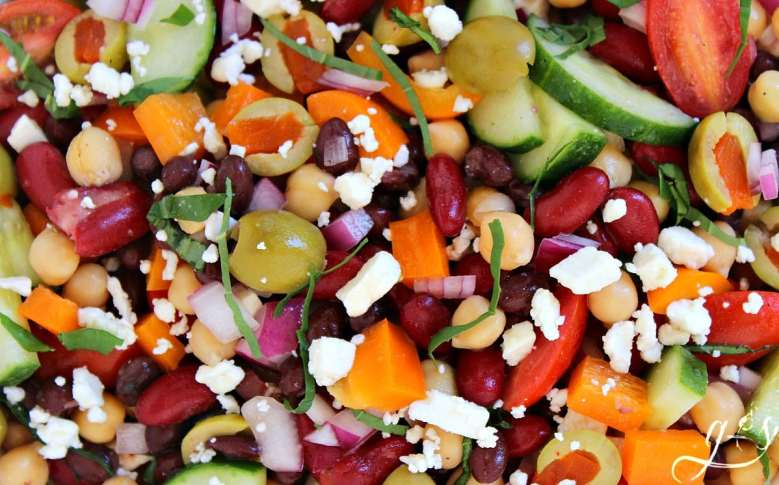 The BEST Mediterranean Tri-Bean Salad | This healthy and easy three bean vegetable salad has all the right flavors. The light and tangy dressing is the icing on the cake in this gluten-free recipe. Canned black, kidney, and garbanzo (chickpeas) combine with fresh cucumber, tomatoes, and peppers to produce a clean eating side dish or vegetarian meal. Low carb recipes like this are exactly what you need if weight loss is a goal!