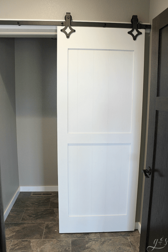How to DIY Your Own Barn Doors | We chose to hang two barn doors in our new home, one chalk board painted and one gel stained. You can do this project on the cheap with this tutorial. These sliding doors in our master suite and laundry room are modern yet rustic and farmhouse yet classic. The black industrial hardware and quiet floor guide work incredibly well. Plus they add so much style on a budget! #bathroom #bedroom #homedecor
