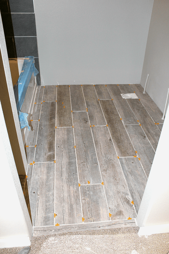 """Photo of completed tile floor planks in bathroom with 1/4"""" spacers."""