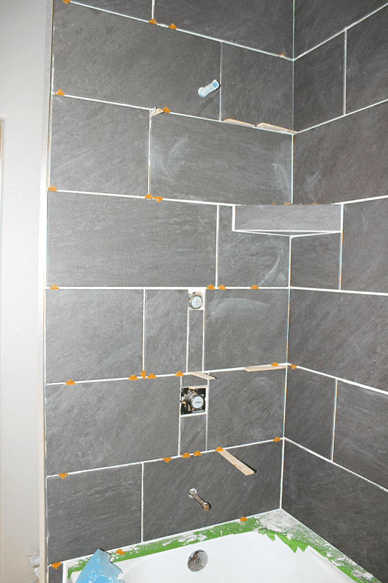 Photo of cut tiles around pipes and valves in shower surround.