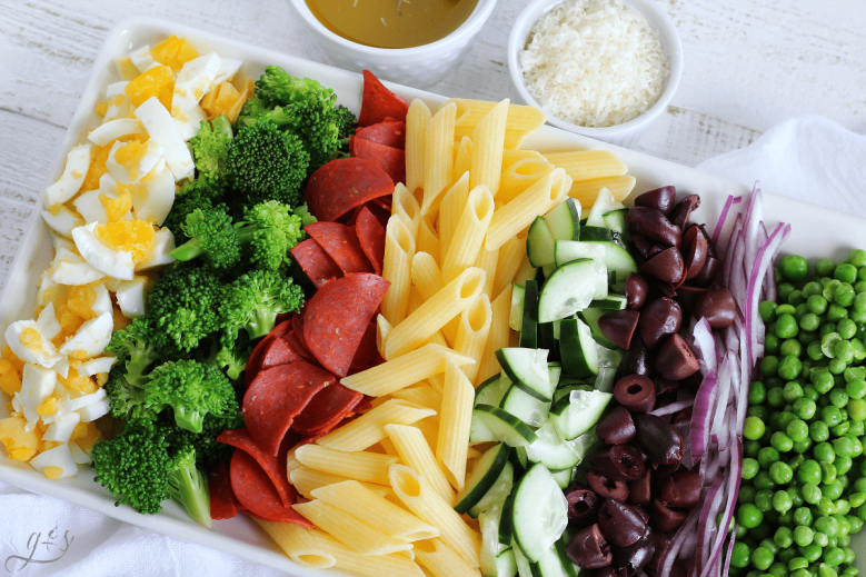 Close up shot of a tray of ingredients for a Gluten Free Pasta Salad loaded with vegetables.