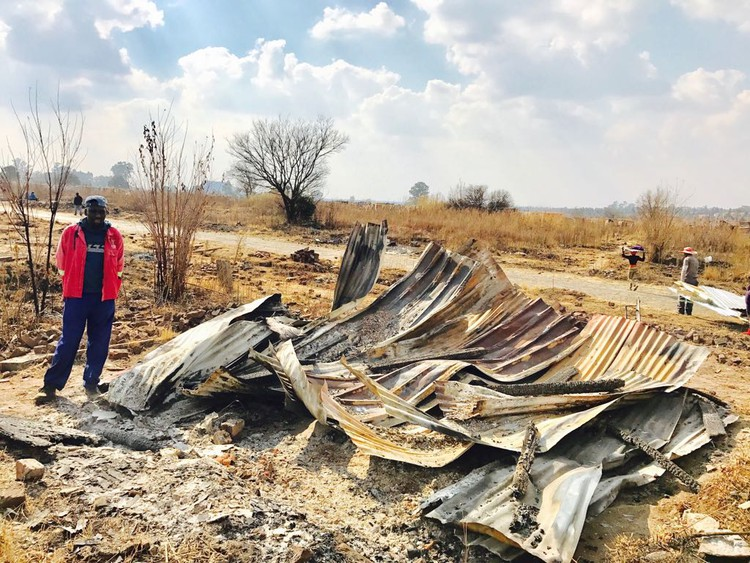 Photo of man standing next to burnt shack