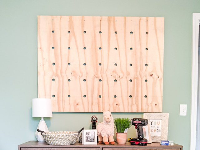 Unpainted pegboard wall above nursery dresser