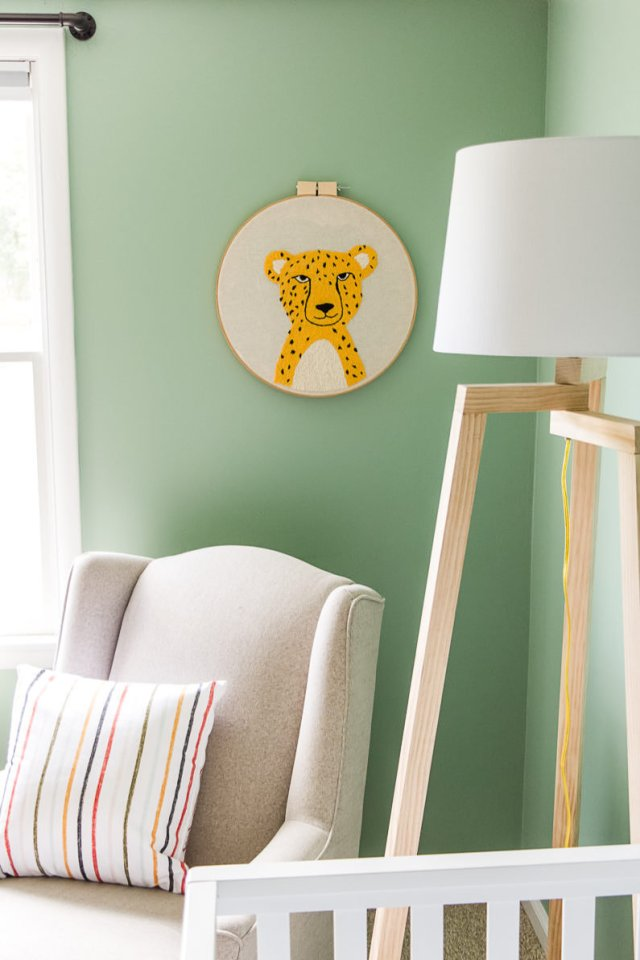 DIY embroidered cheetah wall art, geometric floor lamp with white shade, linen glider with colorful pillow