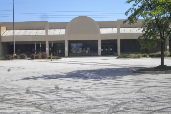 Photo of vacant lot and dilapidated grocery store.