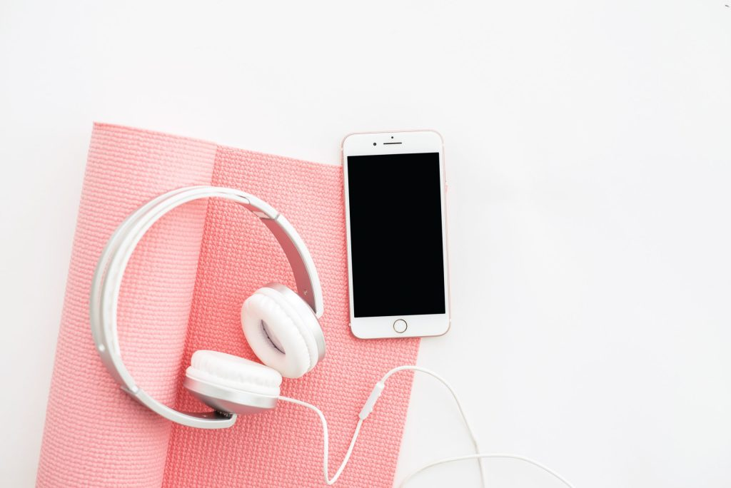Pink yoga mat with phone and headphones laying on top