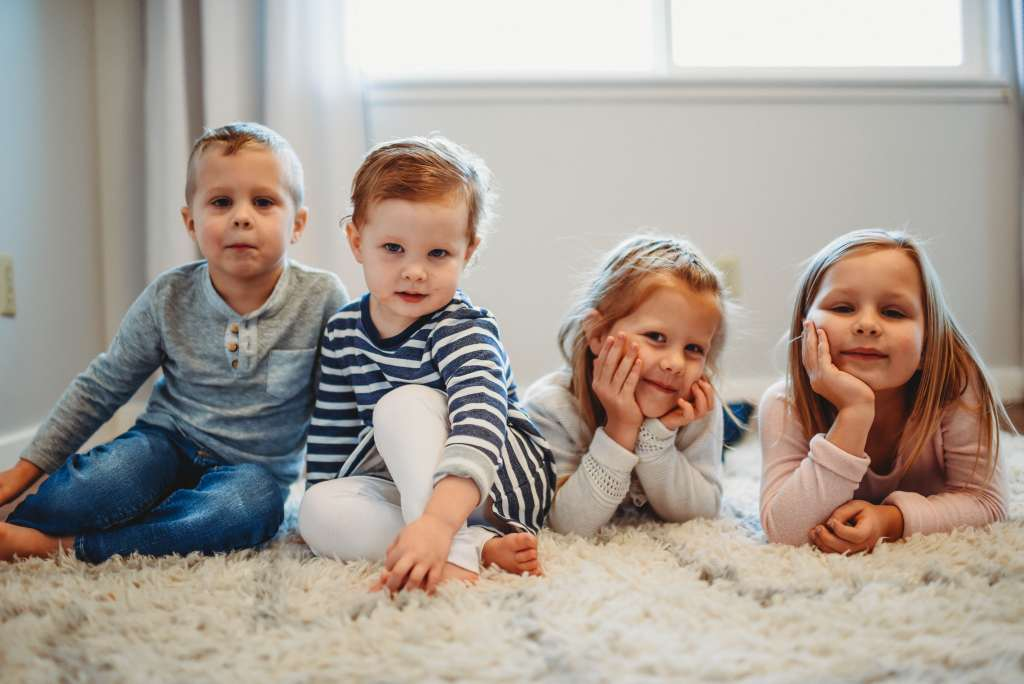 four kids sitting on the floor smiling