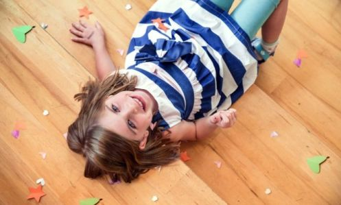 Little girl laying on a wood floor with paper shapes cut out around her on the floor