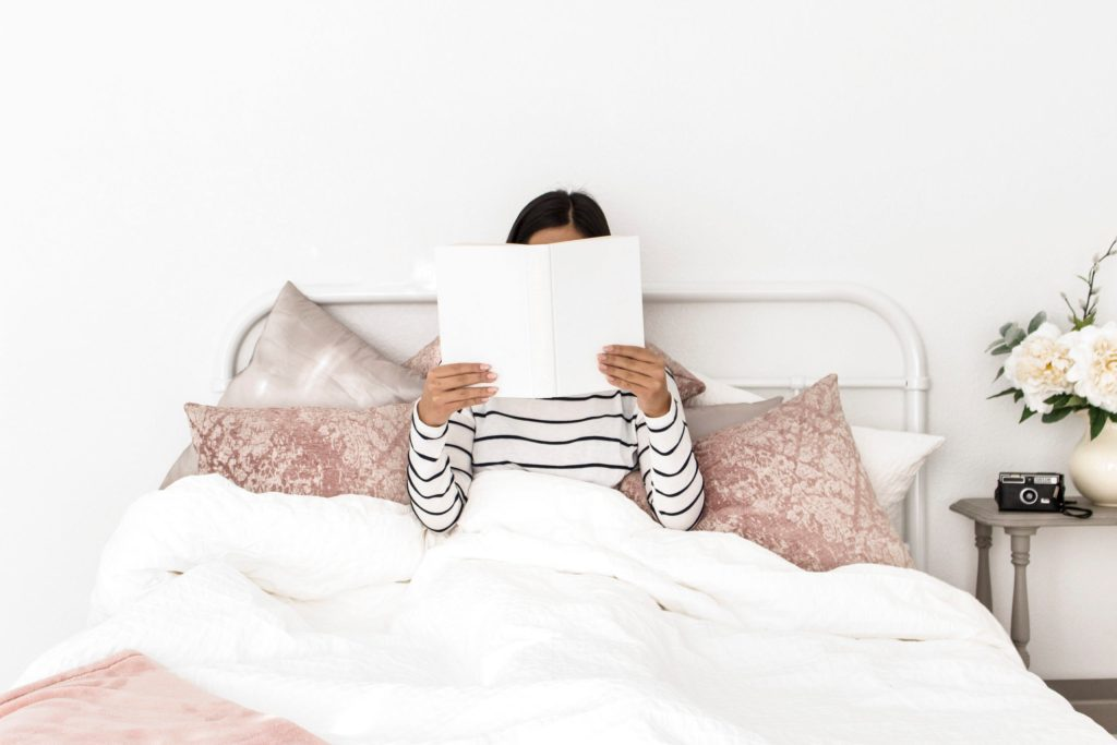 woman wearing a black and white striped top, sitting in bed reading a book