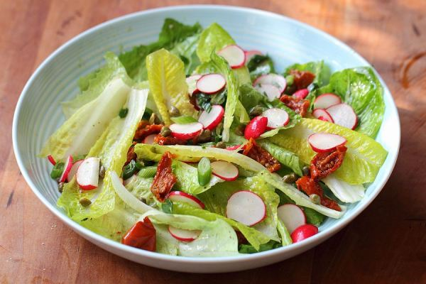 Lettuce salads with radishes, dried tomatoes and capers