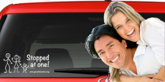 "couple smiles in front of their ""stopped at one"" auto decal"