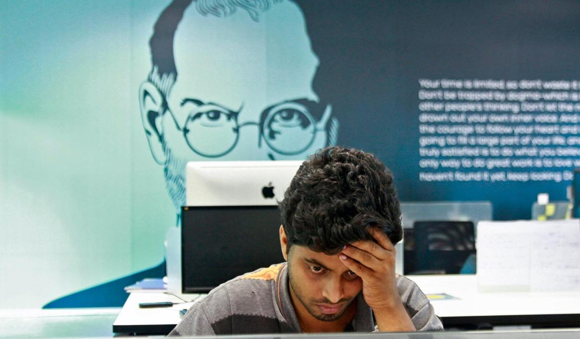 An employee works on a computer terminal against the backdrop of a picture of late Apple cofounder Steve Jobs at the Startup Village in Kinfra Hi-Tech Park. Credit: Reuters/Sivaram V