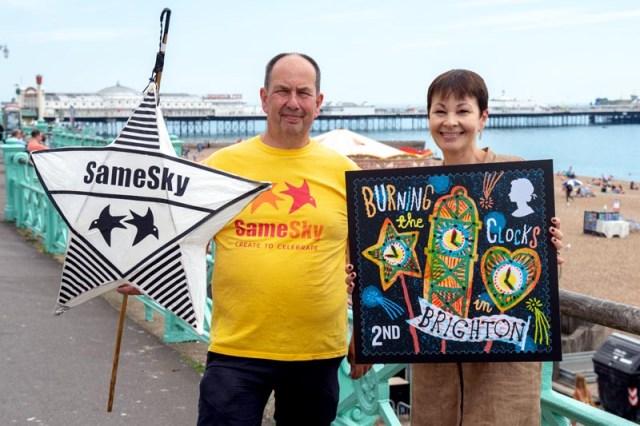 Caroline Lucas MP and John Varah holding a stamp on Brighton sea front