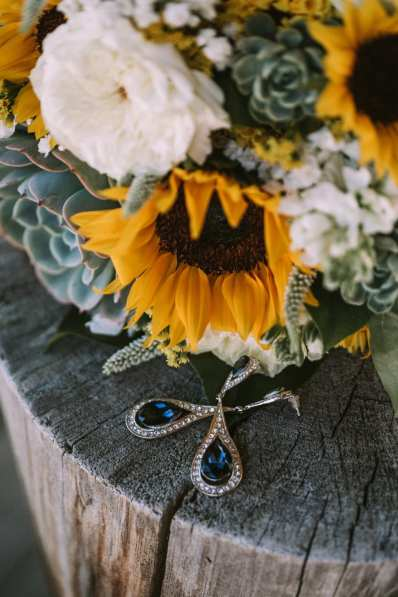 The Bride's Blue teardrop earrings sitting on a stump near her succulent and sunflower bouquet on a wedding day at Reeder's Alley in Helena, Montana.