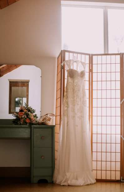 Lace wedding dress hanging on a rice paper room separator by a window in the ready room. Next to green vanity that has a bouquet and the brides white wedge sandals