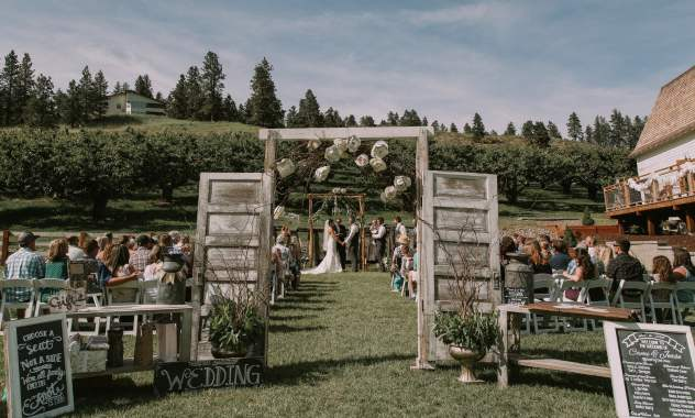 Hampton Hideaway ceremony area with orchard and doors near the white barn