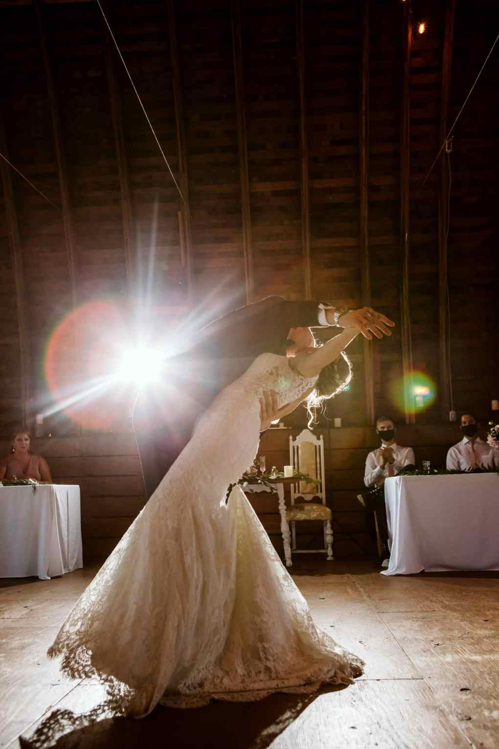 bride and groom dancing at reception with guests wearing a mask
