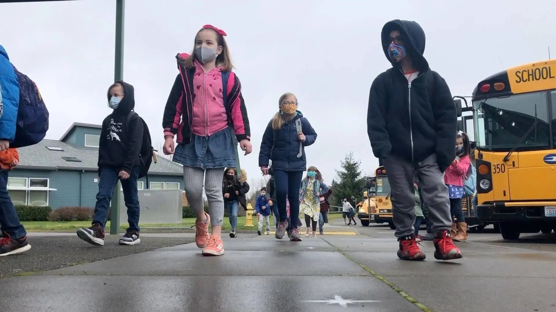 Elementary students walking away from a bus, wearing COVID-19 masks.