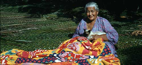 Woman sewing a tivaevae, quit. Photo take on Rarotonga, Cook Islands. Photo from the Alexander Turnbull Library Archive provided by Wikimedia Commons.