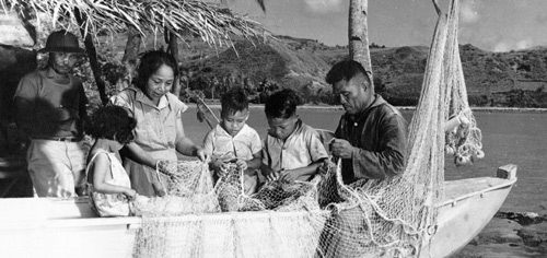 Family mending their talaya. Photo from the Micronesian Area Research Center (MARC) courtesy of Dr. Anne Hattori.