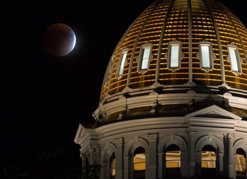 A perigee full moon, or supermoon, is seen during a total lunar eclipse behind the Colorado State Capitol Building on Sunday, Sept. 27, 2015, in Denver. The combination of a supermoon and total lunar eclipse last occurred in 1982 and will not happen again until 2033. Photo Credit: (NASA/Bill Ingalls)