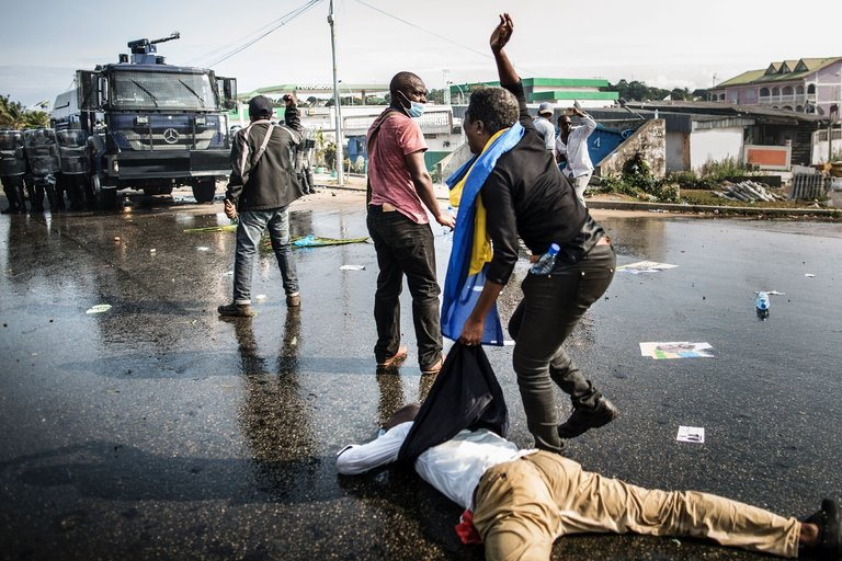 A supporter of the opposition leader Jean Ping lay wounded in Libreville on Wednesday during clashes with riot police.