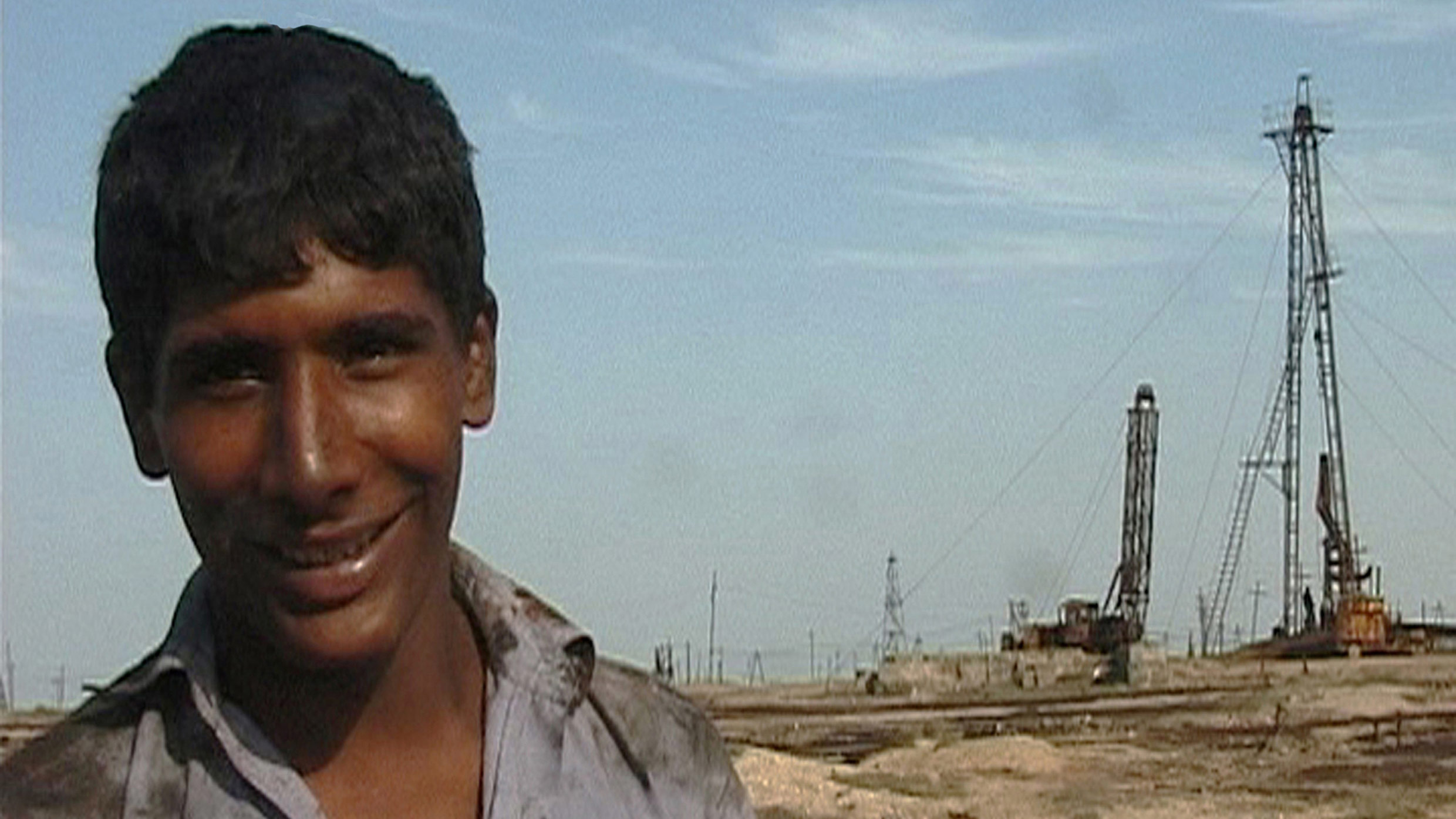 Image of a boy in front of an oil well, a still from Ursula Biemann's Black Sea Files