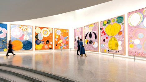 Visitors in the Guggenheim museum standing in front of colorful paintings by Hilma af Klint