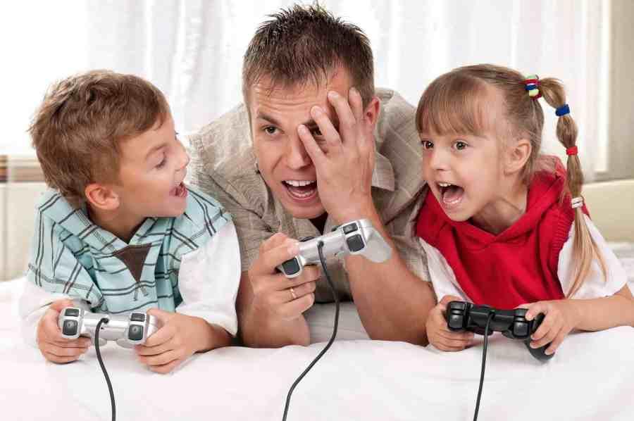 Imagem de pai e filhos jogando video game.