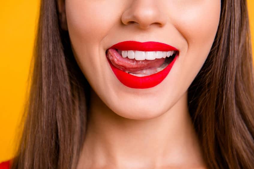 Rosto de mulher de batom vermelho passando a língua nos dentes