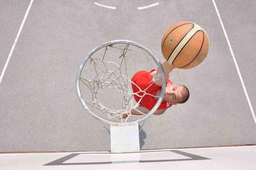 Imagem de homem jogando basquete, fazendo cesta.