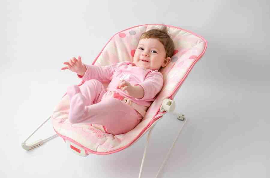Bebê vestida de rosa sentada em uma cadeirinha de balanço rosa sobre o chão