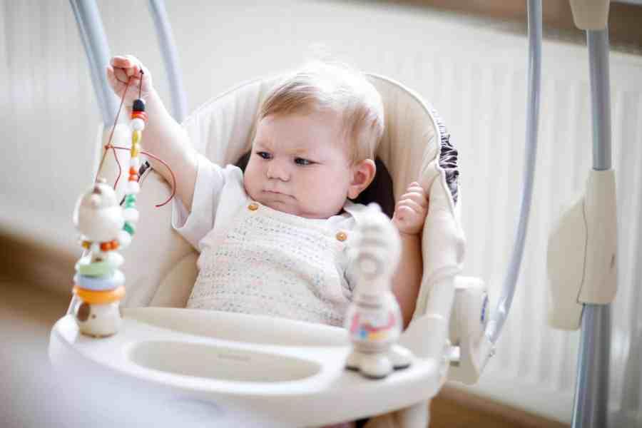 Bebê brinca com chocalho em cadeirinha de descanso