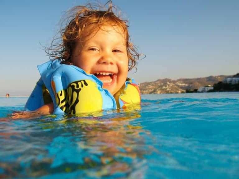 Imagem de bebê sorrindo dentro de piscina.