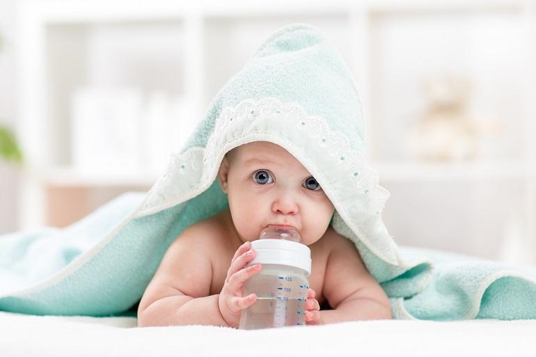 Bebê com toalha na cabeça tomando mamadeira.