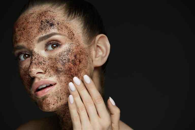 Imagem de mulher passando esfoliante do rosto.