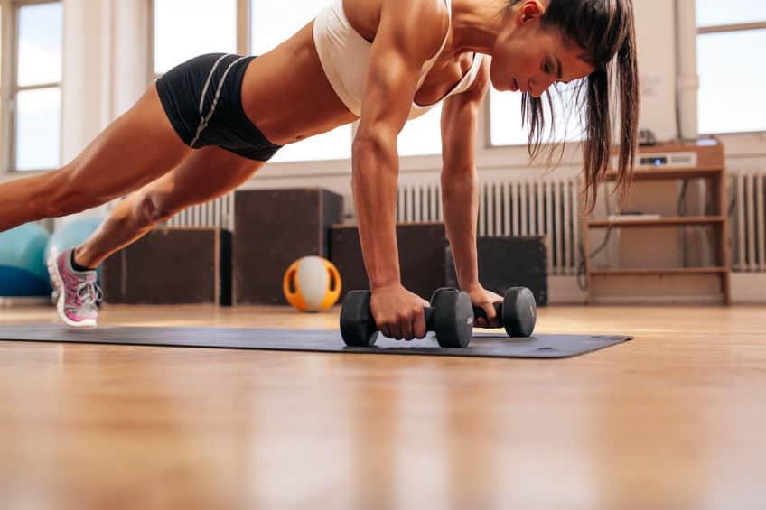 Imagem de mulher treinando com barras de peso.