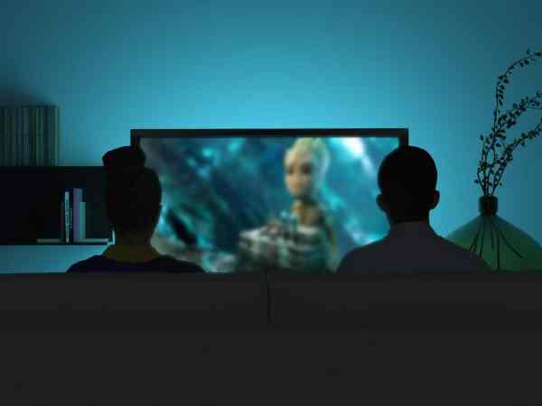 Imagem de pessoas assistindo TV com home theater.